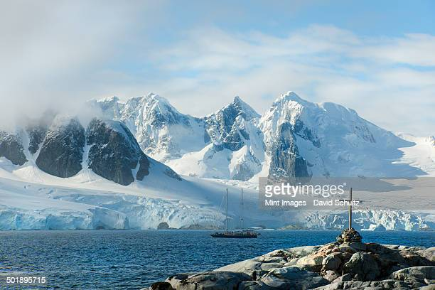 A cross and grave on a hilltop overlooking the snow capped peaks of the mountains on Petterman island. A tall masted ship in the channel.