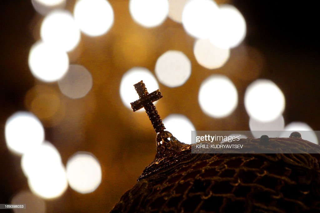 A cross atop Russian Orthodox priest's headgear is seen against lights during a religious service marking Saints Cyrilius and Methodius' Day in...