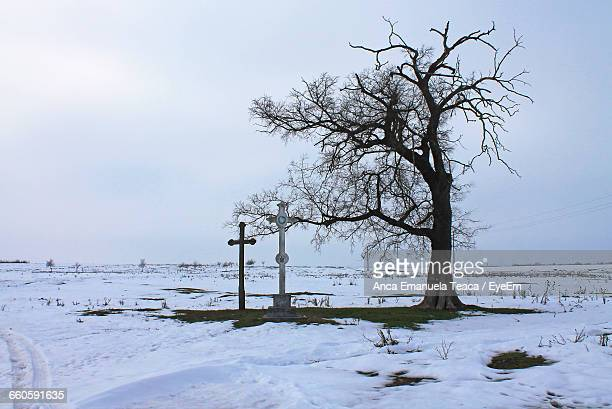 Cross By Bare Tree On Snowy Field Against Sky