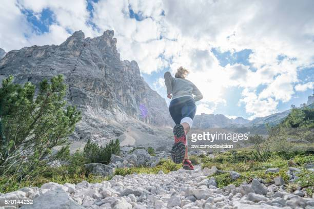 Cross country running female exercising in the Dolomites in Italy, people jogging concept