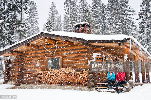 Cross country skiers at a log cabin in falling snow.