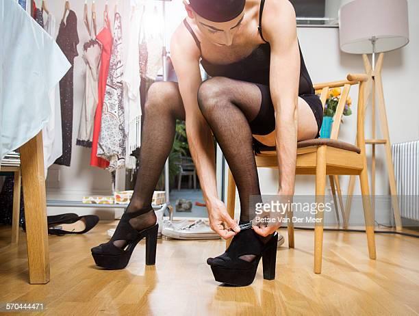 Cross dresser puts on high heel shoes.