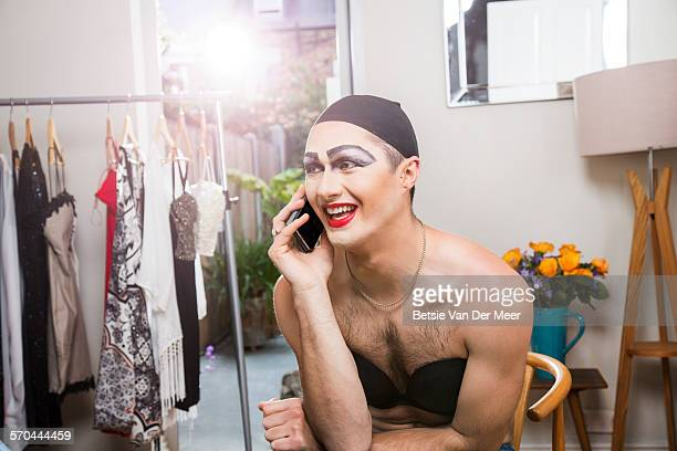 Cross dresser speaking on phone in dressing room