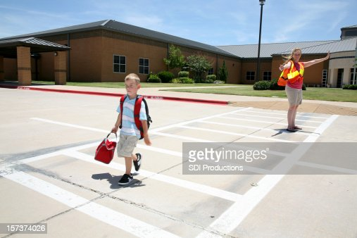 Cross Guard Helping Boy Walk Across The Street At School
