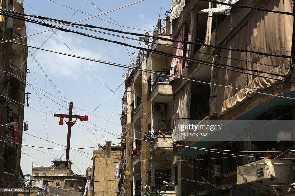 A cross hangs between electricity cables in a Beirut suburb Christian dominated neighborhood on May 26, 2016. / AFP / PATRICK BAZ
