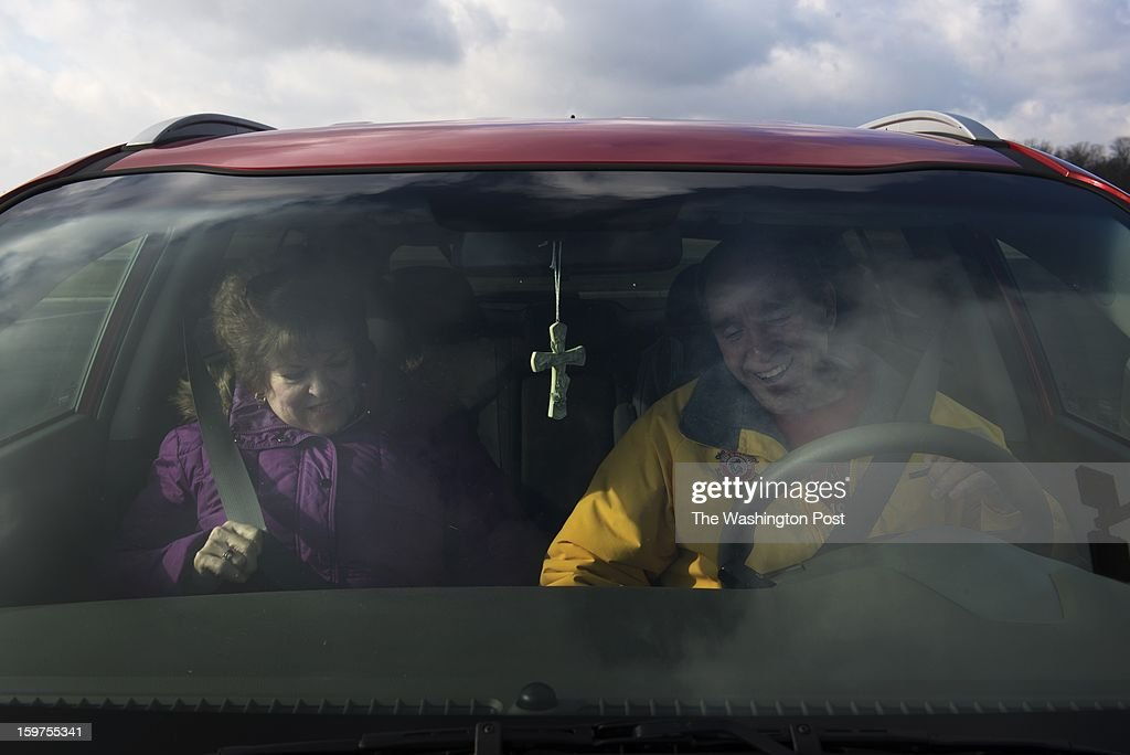 A cross hangs from the rear view mirror in the SUV of Sally and Bill Herr on January 17 in Fremont, Ohio. The Herr's are actively engaged with the Christian church.