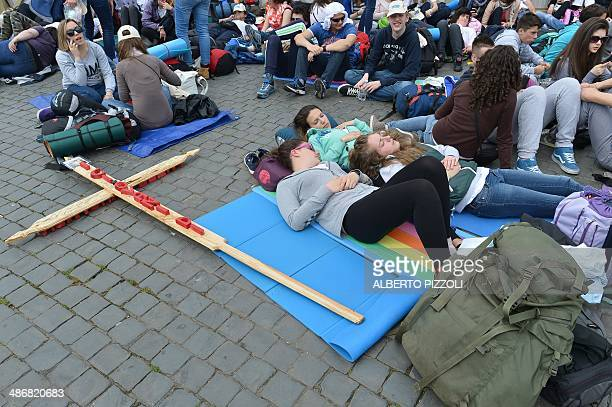 A cross is seen on the ground as people camp on St Peter's square on April 26 2014 at the Vatican a day before the canonisation of late Popes John...