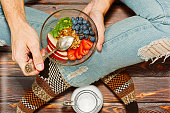 Young person in torn worn jeans cross legged on rural style wooden floor with a bowl of fresh healthy breakfast - granola with apple, kiwi, strawberry, blueberry and almonds. First person view.