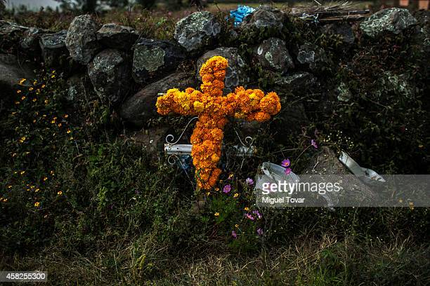 A cross made with cempasuchil flowers is seen outside a cemetery at the outskirt of Patzcuaro which people remember those relatives and friends that...