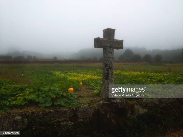 Cross On Grassy Field Against Sky During Foggy Weather