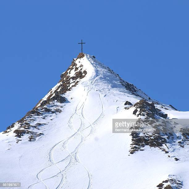 Cross On Top Of Snow Covered Mountain Peak