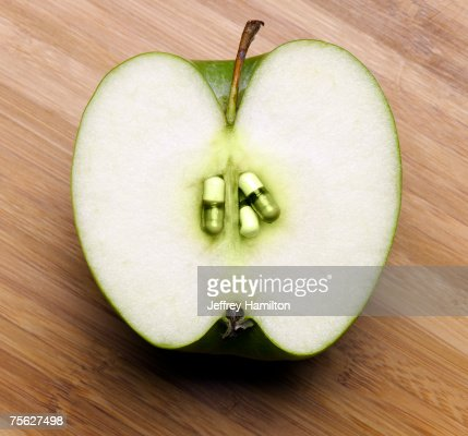 Cross section of apple with pills in place of seeds : Stock Photo