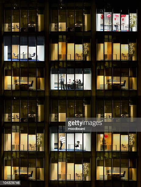 Cross section of office block with people working, view from building exterior (full frame)