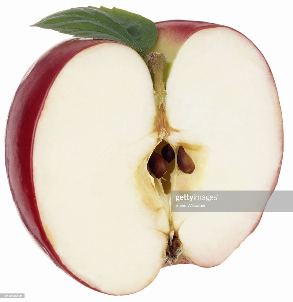 A cross section of red apple showing pits and leaf : Stock Photo