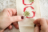 Cross Stitch with Hands Holding Needle and Thread