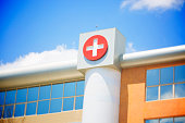 A white on red Red cross symbol on a modern hospital building exterior