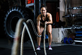 Female training with rope in gym