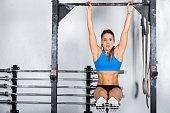 Horizontal color image of woman exercising on gymnastic bar.