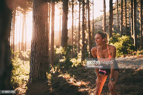 Cross-country runner resting on a morning trail run on mountain