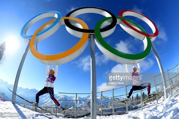Crosscountry skiers Sophie Caldwell and Sadie Bjornsen of the United States hang from the Olympic rings ahead of the Sochi 2014 Winter Olympics at...