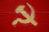 Crossed hammer and sickle painted on wall, close-up