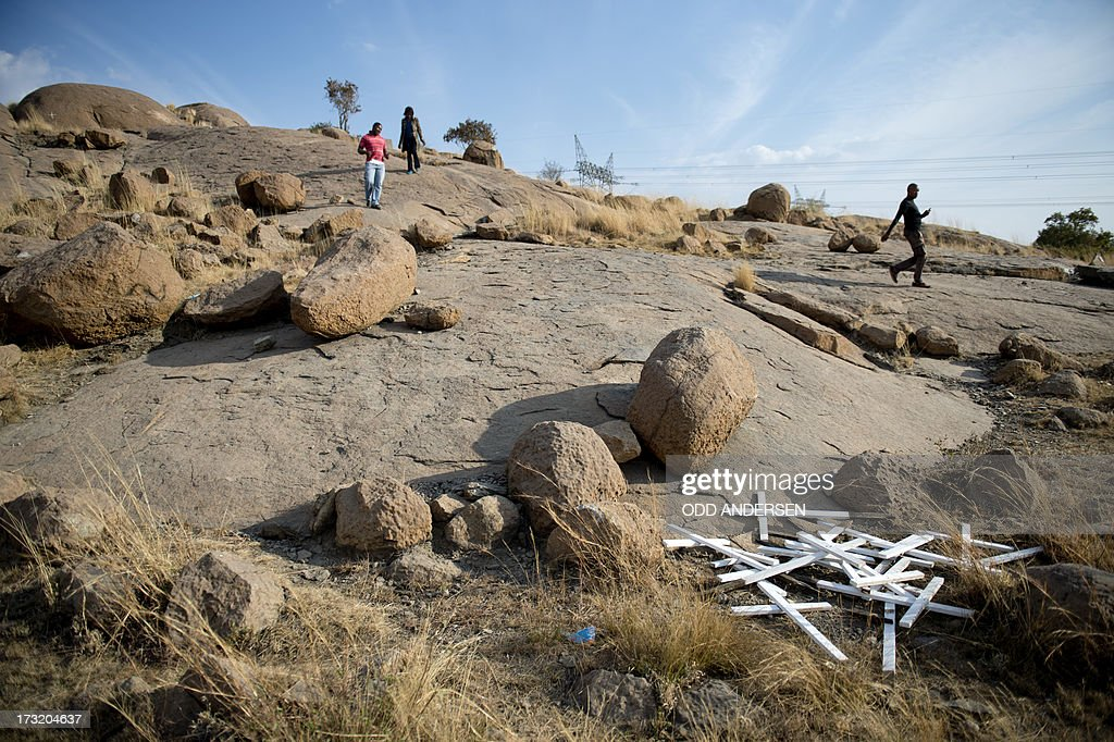 Crosses are seen on July 9, 2013 at the bottom of the hill where 14 of 34 miners were killed by police during a strike in 2012 in the Nkaneng shantytown next to the platinum mine, run by British company Lonmin, in Marikana. On August 16, 2012, police at the Marikana mine open fire on striking workers, killing 34 and injuring 78, during a strike was for better wages and living conditions. Miners still live in dire conditions despite a small wage increase.