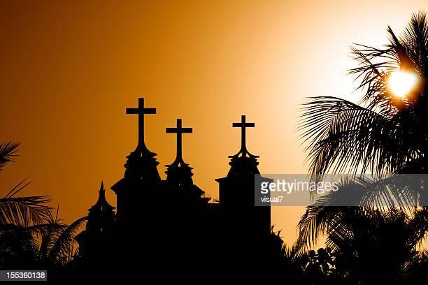 Croix au coucher du soleil avec palmiers