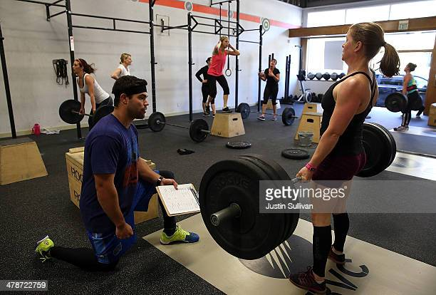 CrossFit coach Kory Cook watches Erin Lindheim do a deadlift during a CrossFit workout at Ross Valley CrossFit on March 14 2014 in San Anselmo...