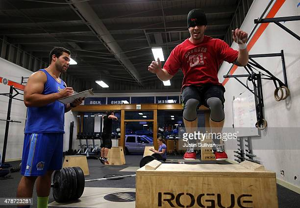 CrossFit coach Kory Cook watches Jason Stanislawczyk do box jumps during a CrossFit workout at Ross Valley CrossFit on March 13 2014 in San Anselmo...