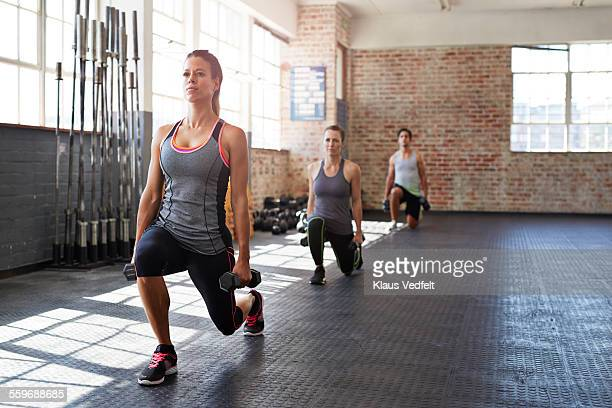 Crossfitters doing lunges with small weights