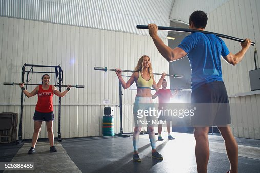 Crossfitters working out with bar in group class
