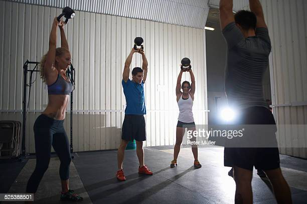 Crossfitters working out with kettlebell in group class