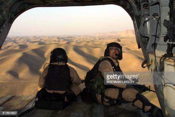 Crossing by air over hills into Afghanistan from Tajikistan United States Special Operations soldiers keep watch from the open back end of a US Army...