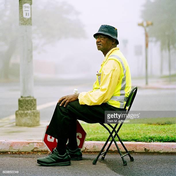 Crossing guard sitting at crosswalk