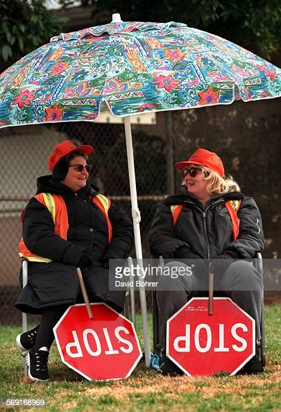 Crossing guards Susan Espinoza and Judith Smith at Hazeltine Avenue Elementary School in Van Nuys bundle up and hide from the rain as they wait for...