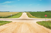 Crossroads intersection of a lonely country gravel dirt road in rural countryside. It intersects a paved highway and is flanked by agricultural farm fields of corn and soybean crops. For moving forwar