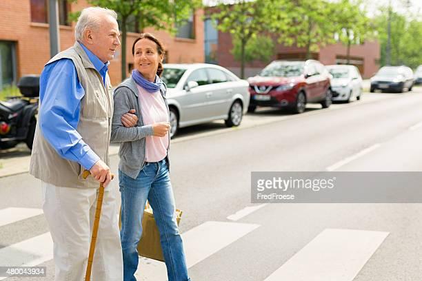 Fußgängerübergang – senior Frau und fürsorgliche Sie zu Fuß im Freien