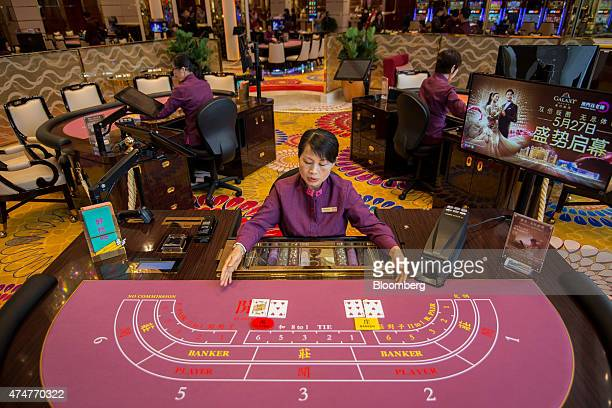 A croupier arranges cards on a baccarat table inside the Broadway Macau casino developed by Galaxy Entertainment Group Ltd in Macau China on Tuesday...
