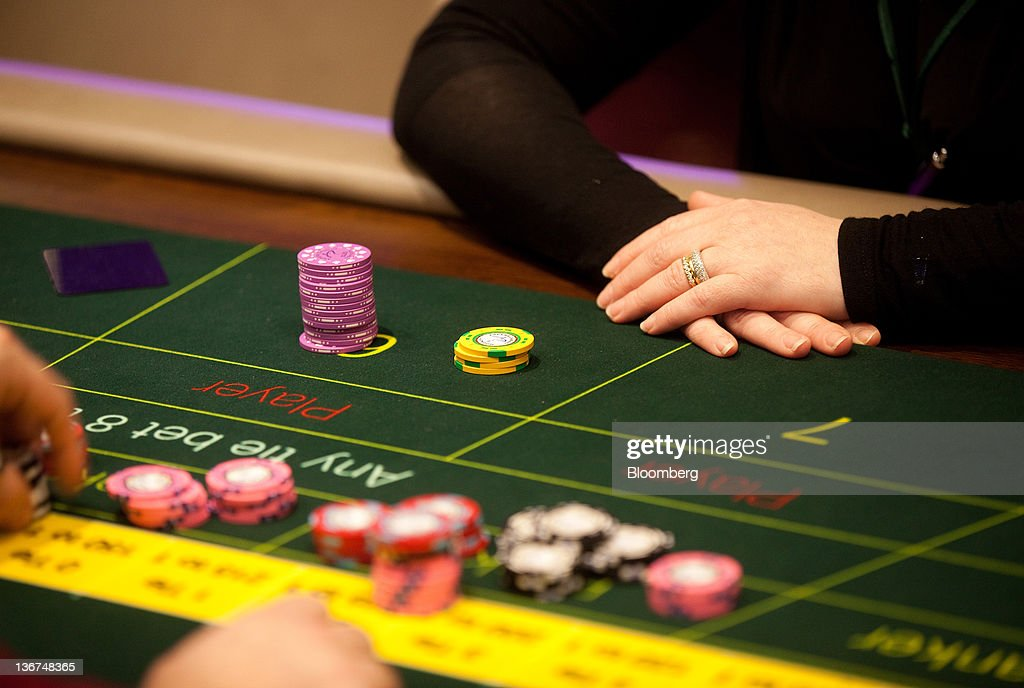 A croupier arranges gambling chips on a card table at Aspers Casino at Westfield Stratford City Mall in London, U.K. on Wednesday, Jan. 11, 2012. Westfield Group agreed to sell its 75 percent interest in the Broadmarsh shopping center to Capital Shopping Centres for 55 million pounds. Photographer: Simon Dawson/Bloomberg via Getty Images
