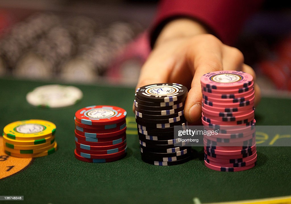 A croupier arranges gaming chips on a card table at Aspers Casino at Westfield Stratford City Mall in London, U.K. on Wednesday, Jan. 11, 2012. Westfield Group agreed to sell its 75 percent interest in the Broadmarsh shopping center to Capital Shopping Centres for 55 million pounds. Photographer: Simon Dawson/Bloomberg via Getty Images