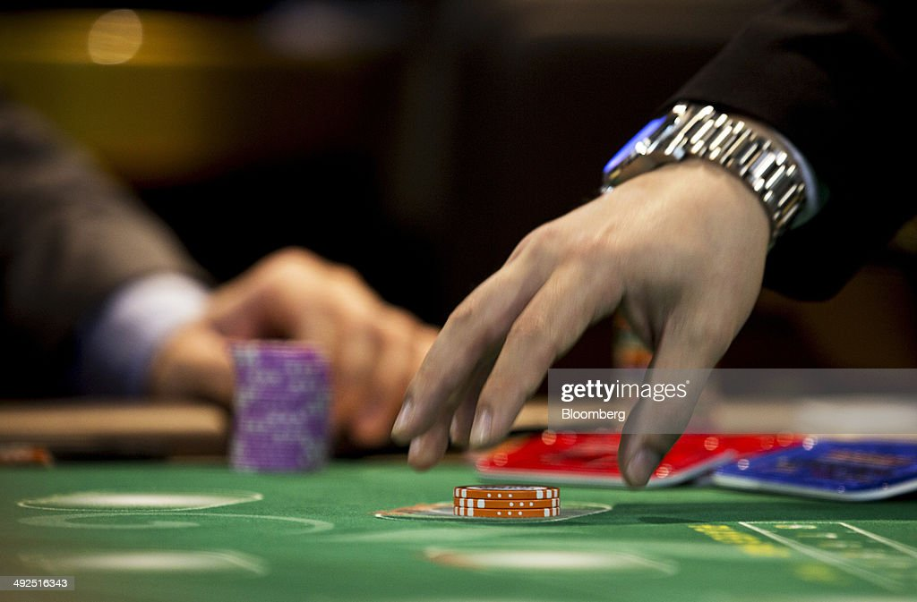 A croupier collects gaming chips at the Global Gaming Expo (G2E) inside the Venetian Macao resort and casino, operated by Sands China Ltd., a unit of Las Vegas Sands Corp., in Macau, China, on Tuesday, May 20, 2014. The gaming expo runs through May 22. Photographer: Brent Lewin/Bloomberg via Getty Images