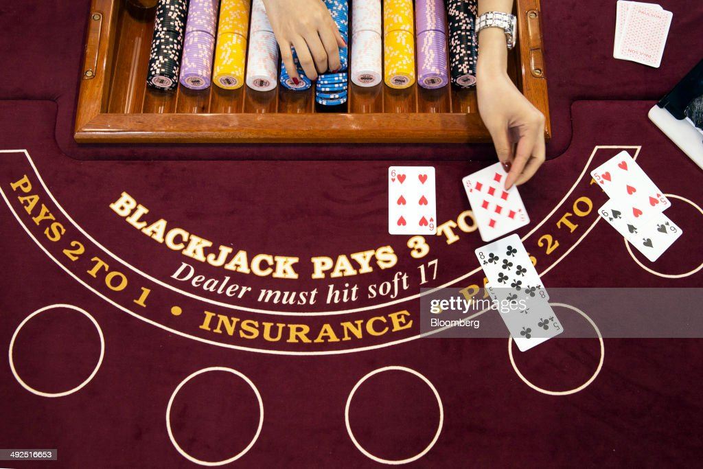 A croupier deals a card on a blackjack table at a Gaming Partners International Corp. (GPI) booth at the Global Gaming Expo (G2E) inside the Venetian Macao resort and casino, operated by Sands China Ltd., a unit of Las Vegas Sands Corp., in Macau, China, on Tuesday, May 20, 2014. The gaming expo runs through May 22. Photographer: Brent Lewin/Bloomberg via Getty Images