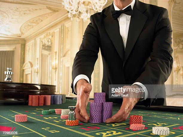 Croupier gathering chips at Roulette table in casino
