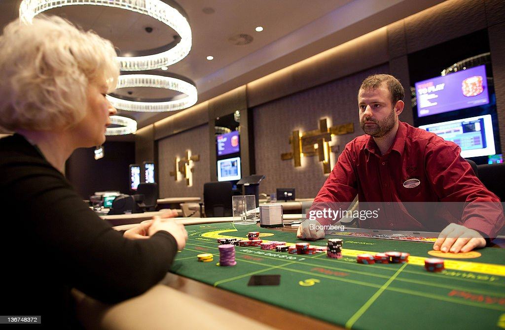 A croupier (right) is seen at a card table during a staff training session at Aspers Casino at Westfield Stratford City Mall in London, U.K. on Wednesday, Jan. 11, 2012. Westfield Group agreed to sell its 75 percent interest in the Broadmarsh shopping center to Capital Shopping Centres for 55 million pounds. Photographer: Simon Dawson/Bloomberg via Getty Images