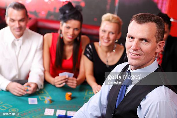 Croupier looking at camera, behind his gamblers playing Blackjac
