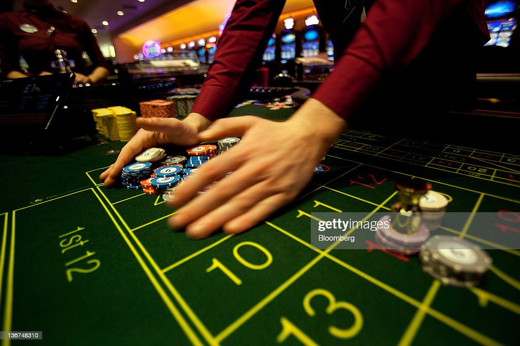 A croupier removes losing gaming chips from a roulette table at Aspers Casino at Westfield Stratford City Mall in London, U.K. on Wednesday, Jan. 11, 2012. Westfield Group agreed to sell its 75 percent interest in the Broadmarsh shopping center to Capital Shopping Centres for 55 million pounds. Photographer: Simon Dawson/Bloomberg via Getty Images