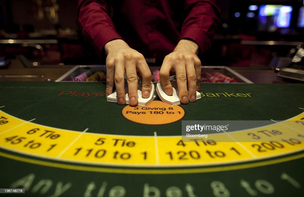 A croupier shuffles a deck of cards at Aspers Casino at Westfield Stratford City Mall in London, U.K. on Wednesday, Jan. 11, 2012. Westfield Group agreed to sell its 75 percent interest in the Broadmarsh shopping center to Capital Shopping Centres for 55 million pounds. Photographer: Simon Dawson/Bloomberg via Getty Images