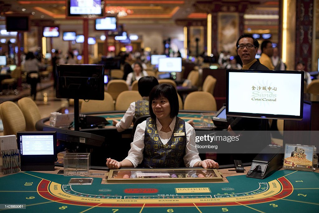 A croupier sits at her baccarat table in the Sands Cotai Central casino resort on its opening day in Macau, China, on Wednesday, April 11, 2012. Las Vegas Sands Corp. Chairman Sheldon Adelson plans to spend $35 billion on building Spanish gambling resorts over nine years and will add a new Macau location to expand globally. Photographer: Jerome Favre/Bloomberg via Getty Images