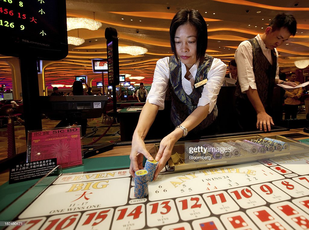 A croupier stacks betting chips in the Sands Cotai Central casino resort, owned by Sands China Ltd., a unit of Las Vegas Sands Corp., in Macau, China, on Thursday, Sept. 20, 2012. Billionaire Sheldon Adelson's casino operator Las Vegas Sands Corp. plans to invest at least $2.5 billion to build its fifth resort in Macau, where gambling revenue is forecast to rise to $100 billion by 2020. Photographer: Daniel J. Groshong/Bloomberg via Getty Images