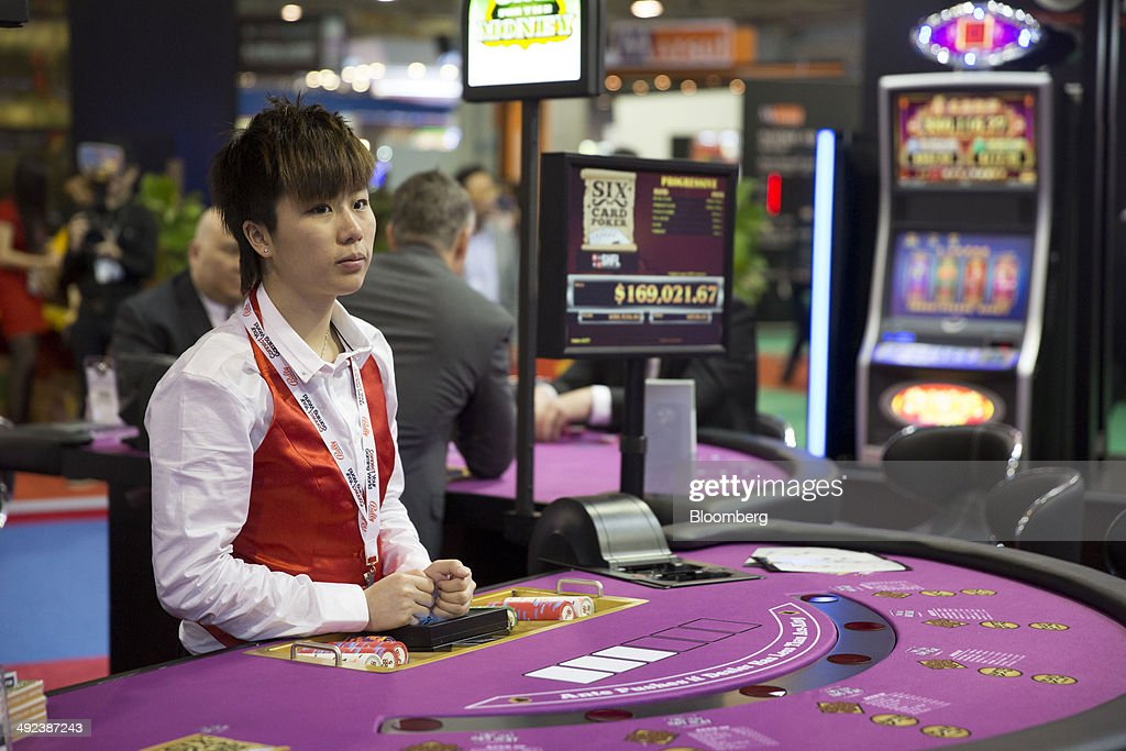 A croupier stands at a poker table at the Bally Technologies Inc. booth at the Global Gaming Expo (G2E) inside the Venetian Macao resort and casino, operated by Sands China Ltd., a unit of Las Vegas Sands Corp., in Macau, China, on Tuesday, May 20, 2014. The gaming expo runs through May 22. Photographer: Brent Lewin/Bloomberg via Getty Images